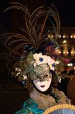 与花和羽毛帽子的面具在威尼斯狂欢节 图库摄影