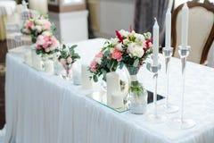 与花和蜡烛的婚姻的镜子桌接近 免版税库存图片
