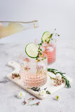 与花和被切开的石灰的桃红色新鲜的鸡尾酒在石书桌背景 库存图片