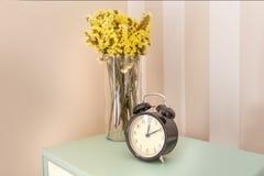 与花和闹钟的Nightstand 库存照片