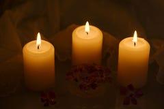 与花和鞋带桌布的蜡烛 免版税图库摄影