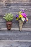 与花和麦子耳朵的两个柳条筐在墙壁上 图库摄影