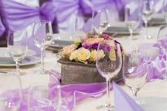 与花和玻璃的婚礼桌 图库摄影
