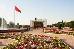与花圃的主要城市广场丙氨酸太和吉尔吉斯斯坦的国旗 免版税库存图片