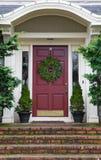 与花圈的紫红色门 库存图片