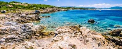 与花岗岩岩石的美丽的costline和在波尔图Pollo,撒丁岛,意大利的惊人的天蓝色的水 图库摄影