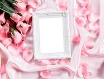 与花束甜桃红色玫瑰花瓣的空的照片框架在软的桃红色丝织物,浪漫史和爱拟订概念 免版税库存照片