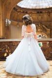 与花束的时髦的豪华新娘跳舞在富有的内部背景在老大厦的 免版税库存图片