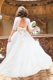 与花束的时髦的豪华新娘跳舞在富有的内部背景在老大厦的 库存照片
