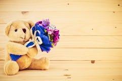 与花束的熊在手中 免版税图库摄影