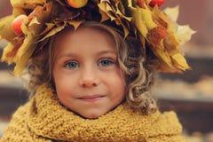 与花束的逗人喜爱的可爱的小孩女孩画象秋叶和花圈走室外在公园 库存照片