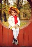 与花束的逗人喜爱的可爱的小孩女孩画象秋叶和花圈走室外在公园 免版税库存照片