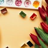 与花束红色郁金香、水彩小试管和调色板的艺术家工作区在苍白桃子柔和的淡色彩背景 您的设计的地方 免版税库存照片