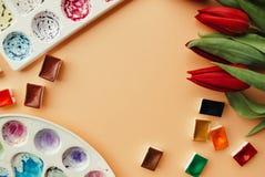 与花束红色郁金香、水彩小试管和调色板的艺术家工作区在苍白桃子柔和的淡色彩背景 您的设计的地方 库存图片