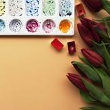 与花束红色郁金香的艺术家工作区,水彩,在桃子背景的调色板与您的文本的地方 平的位置 库存照片