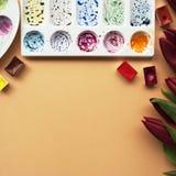 与花束红色郁金香的艺术家工作区,水彩,调色板,在桃子背景的画笔与您的文本的地方 f 免版税图库摄影