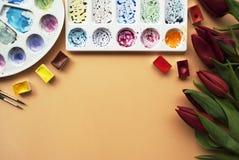 与花束红色郁金香的艺术家工作区,水彩,调色板,在桃子背景的画笔与您的文本的地方 f 免版税库存图片