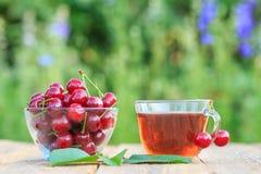 与花梗的红色成熟樱桃果子在玻璃碗和茶 免版税库存照片