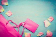 与花瓣的明亮的桃红色纸购物袋在蓝色绿松石破旧的别致的背景,顶视图,文本的,边界地方 总和 免版税库存照片