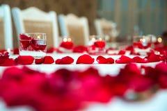 与花瓣的美好的浪漫红色蜡烛 花瓣、蜡烛和玻璃 库存图片