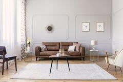 与花瓶和杯子的咖啡桌在与舒适的皮革沙发,时髦的紫色椅子的典雅的客厅内部中间 库存图片