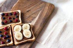 与花生酱和莓果,在木背景的香蕉的多士 库存照片