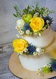 与花的两层的被镀金的婚宴喜饼 库存照片