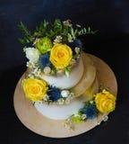 与花的两层的被镀金的婚宴喜饼 免版税图库摄影