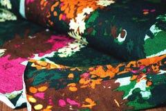 与花的五颜六色的纺织品卷在木 库存图片
