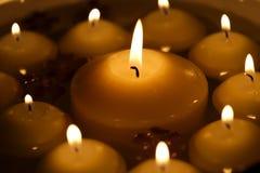 与花的众多的灼烧的蜡烛在水中 免版税库存照片