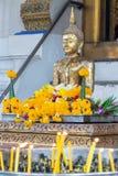 与花的佛教在蜡烛台的雕象和蜡烛 免版税库存图片