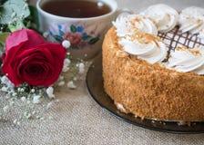 与花的在桌上的蜜糕和茶,盖用粗麻布 免版税库存照片