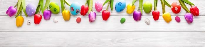 与花的复活节彩蛋在木背景 免版税库存照片