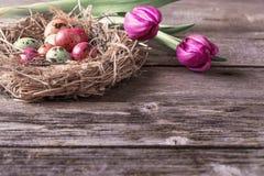 与花的复活节彩蛋巢在土气木背景 免版税库存图片