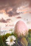 与花的大桃红色鸡蛋在高草 免版税库存图片