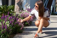 与花的妇女在阳光下火光 免版税图库摄影