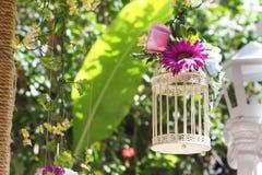 与花的婚姻的装饰鸟笼在自然后面 免版税库存照片