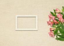 与花的平的被放置的框架在米黄花岗岩背景 库存图片