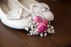与花的新娘shues在桌上 免版税库存图片