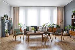 与花的木桌在宽敞生活r的扶手椅子之间 库存照片