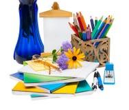 与花的构成在花瓶和学校用品 图库摄影