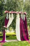 与花的淡紫色婚礼曲拱在仪式地方 免版税库存图片