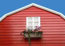 与花的白色窗口在红色谷仓 免版税库存照片