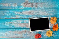 与花的空白的照片框架册页在蓝色木背景 免版税库存图片