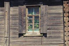 与花的窗口在木房子,俄国乡下里 图库摄影