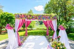 与花的美丽的婚礼曲拱在庭院里 库存照片