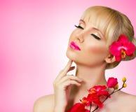 与花的美好的白肤金发的模型 免版税库存照片