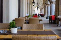 与花的街道咖啡馆在被成拱形的画廊的早晨在欧洲老城市 免版税库存照片