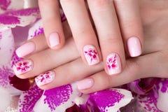 与花的被射击的美好的修指甲在女性手指 钉子设计 特写镜头 免版税图库摄影