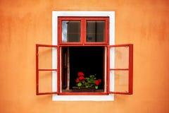 与花的被打开的老红色窗口在橙色墙壁 免版税库存图片